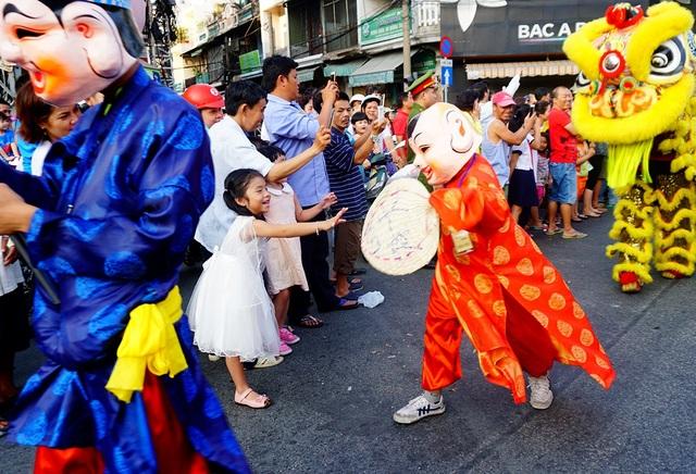 Những em bé thích thú với các nhân vật trong đoàn diễu hành lễ hội Tết Nguyên tiêu.