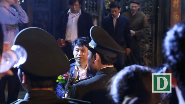 Một người đàn ông nhanh tay xin lộc bước vội vàng ra khỏi đền Thiên Trường