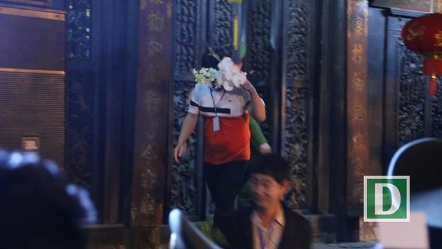Khi thấy ống kính phóng viên hướng về phía mình, người đàn ông này ngay lập tức dùng chiến lợi phẩm là lộc xin được trong đền Thiên Trường che lên mặt