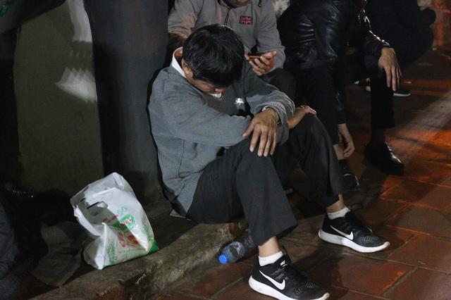 Một nam du khách tựa lưng ngủ gục ngay trong sân đền Thiên Trường.