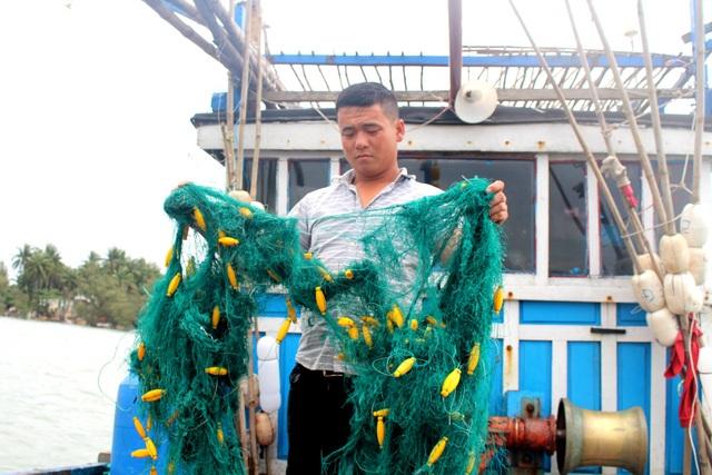 """Ngư dân Nguyễn Tấn Sơn cầm tấm lưới bị những người trên """"tàu lạ"""" cắt hư hỏng."""