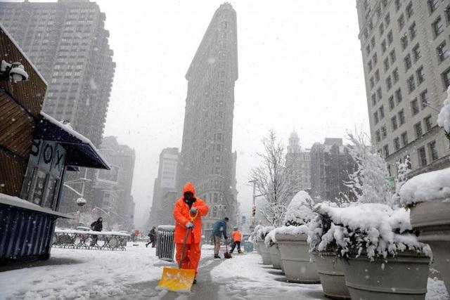 Các công nhân dọn tuyết trước tòa nhà Flatiron ở New York.