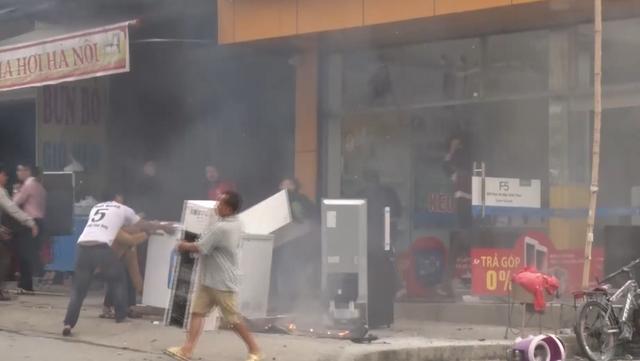 Người dân giúp gia chủ vận chuyển đồ ra khỏi cửa hàng khi ngọn lửa bốc cháy.