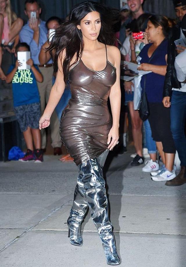 """Ngôi sao truyền hình thực tế Mỹ Kim Kardashian (37 tuổi) đã tái hiện lại ý tưởng thời trang gây tranh cãi của siêu mẫu Kate Moss nhiều năm về sau, khi cô kết hợp một bộ đầm bạc may bằng vải nhựa trong suốt với đôi bốt """"đùi"""" cùng tông."""