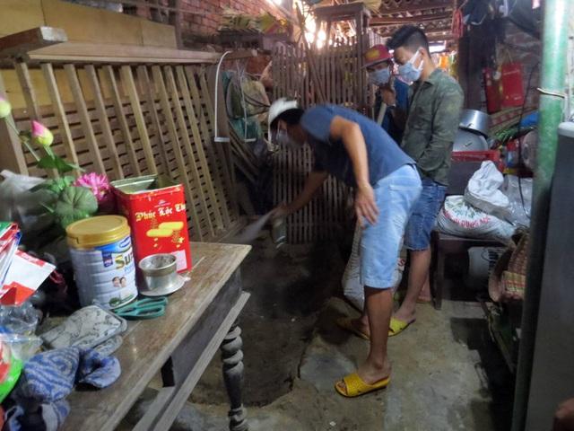 Hàng xóm hỗ trợ ông T vệ sinh lại phần đất chôn bà T