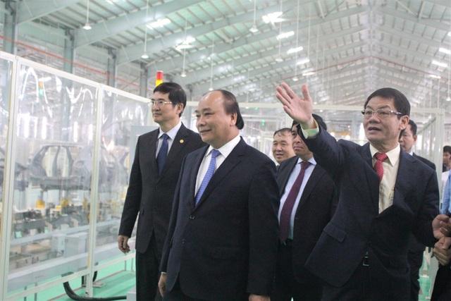 Thủ tướng Nguyễn Xuân Phúc cùng ông Trần Bá Dương (bên phải) đi thăm quan nhà máy sản xuất ô tô Thaco Mazda. (Ảnh: Hồng Vân)