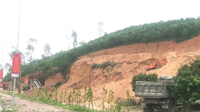 Phía trên đồi một máy múc lớn, phía dưới cả đoàn xe đang chờ để ăn đất.