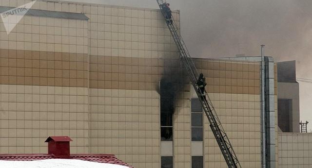 Lực lượng cứu hỏa sử dụng thang để cứu các nạn nhân bị mắc kẹt bên trong trung tâm mua sắm. Tuy nhiên họ vẫn không thể tiếp cận một số căn phòng do nhiệt độ quá cao. (Ảnh: Sputnik)
