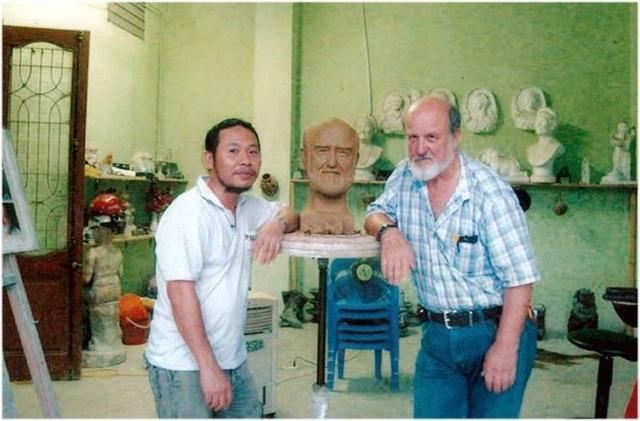 Nhà điêu khắc Trần Minh Tuấn - cha đẻ của bộ tượng 12 con giáp và một vị khách nước ngoài. Ảnh: TL.
