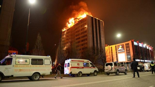 Tầng thượng của tòa nhà cháy ngùn ngụt trong đêm. (Ảnh: Sputnik)