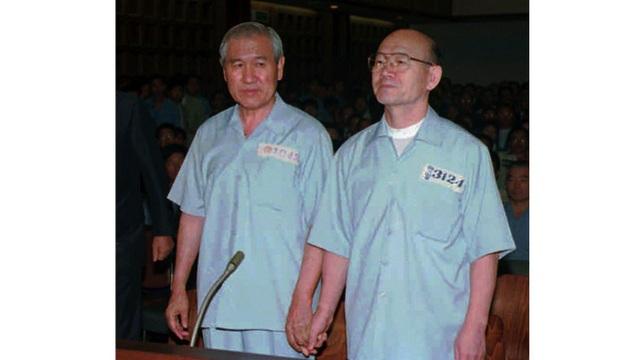 Hai cựu Tổng thống Roh Tae Woo (trái) và Chun Doo Hwan nắm tay nhau trong phiên xét xử tại Tòa án quận Seoul ngày 26/8/1996 (Ảnh: AP)