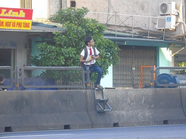Một em học sinh qua đường bằng thang trên giải phân cách
