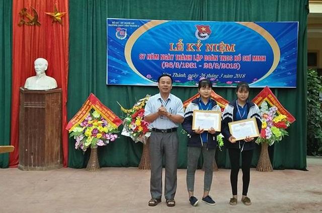 Thầy Nguyễn Văn Thành - Hiệu trưởng Trường THPT Yên Thành 2 trao thư khen cho hai em Vân và Bình.