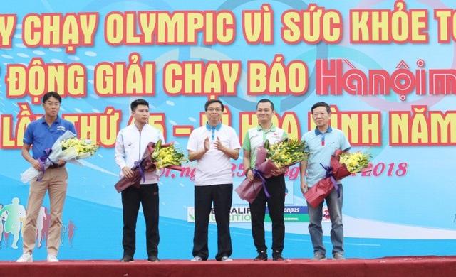 Ông Phạm Tường Huy, Tổng giám đốc Herbalife Việt Nam (áo xanh, thứ hai từ phải sang) nhận hoa cảm ơn từ đại diện Ban tổ chức khi cùng đồng hành, hưởng ứng và truyền tải thông điệp tích cực của Ngày chạy Olympic Run