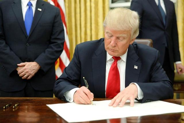 Tổng thống Donald Trump ký một sắc lệnh hành pháp tại Phòng Bầu Dục (Ảnh: Reuters)