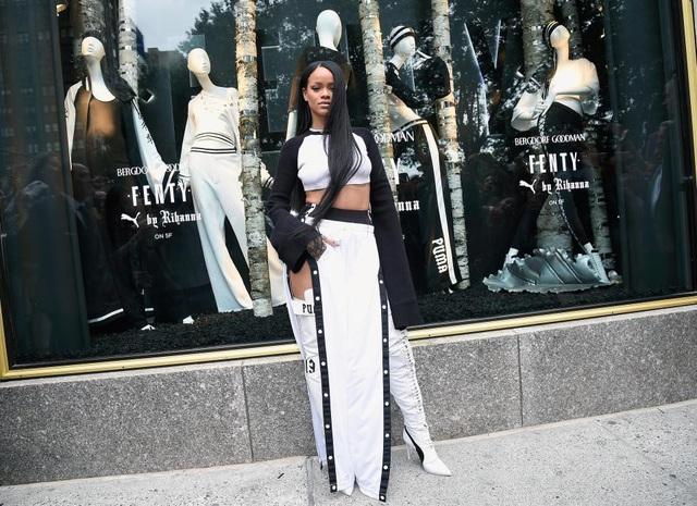 Nữ ca sĩ Rihanna bật tung hết khuy bấm của ống quần để ống xẻ cao tới… đùi và kết hợp với bốt đùi đầy phá cách, cá tính.