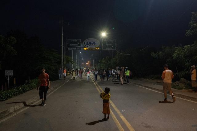 Một cậu bé Venezuela đứng giữa cây cầu biên giới với Colombia. (Ảnh: NYT)