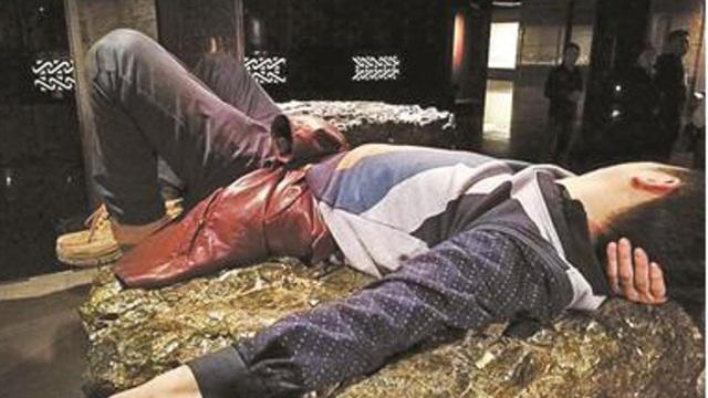 Người đàn ông ngang nhiên nằm ngủ trên khối ngọc bích trong viện bảo tàng. (Ảnh: Sina)