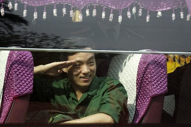 Một tân binh rạng rỡ chào người thân khi đã yên vị trên xe.