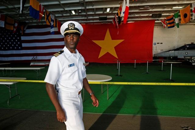 Quốc kỳ Việt Nam và Mỹ được treo cạnh nhau bên trong tàu sân bay USS Carl Vinson. (Ảnh: Reuters)