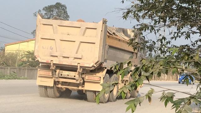 Những chiếc xe trọng tải lớn chất đầy đất, che chắn sơ sài ầm ầm lưu thông trên quốc lộ là nỗi khiếp sợ của người dân.