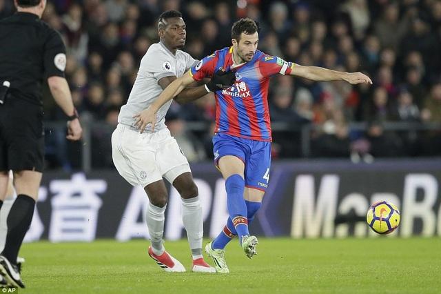 Pogba (trái) cố gắng túm Milivojevic không dể tiền vệ của đối phương thoát đi
