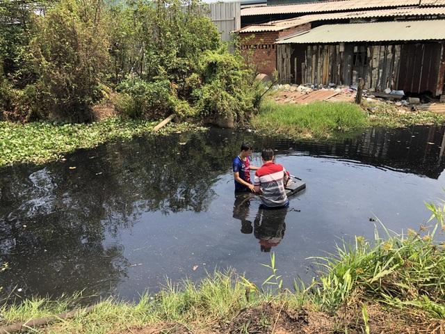 Chiến sĩ cảnh sát ngâm mình giữa kênh nước đen để lắp đặt máy bơm hút nước phục vụ việc chữa cháy