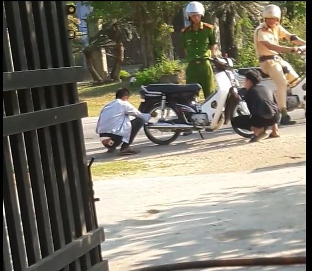 2 thanh niên không đội mũ bảo hiểm khi tham gia giao thông tự chịu phạt bằng cách xì bánh xe dắt bộ (Ảnh: Minh Thùy)