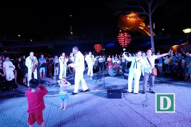 """Ban nhạc Hạm đội 7 Hải quân Mỹ đã biểu diễn hòa nhạc ngay trên đường phố Đà Nẵng, thu hút hàng ngàn người dân và du khách thưởng thức. Nữ binh sĩ Emily Kershow - giọng ca chính của ban nhạc đã dành hai tuần trước đó để luyện hát các ca khúc """"Xin chào Việt Nam"""", """"Nối vòng tay lớn"""" bằng tiếng Việt - phần trình diễn hấp dẫn nhất khi ban nhạc tiếp tục biểu diễn khi thăm các em nhỏ ở làng trẻ SOS - Đà Nẵng và trong các buổi giao lưu văn hóa, thể thao khác của đoàn ở Đà Nẵng"""
