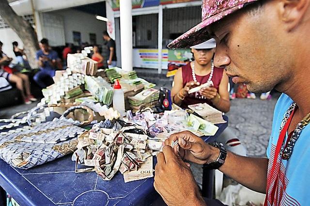 Anh Richard Segovia ngồi gấp thủ công với các loại tiền giấy của Venezuela. (Nguồn: Borneo Bulletin)