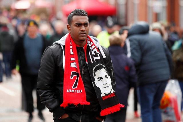 Một cổ động viên của MU với tấm khăn lưu niệm có in hình Sanchez