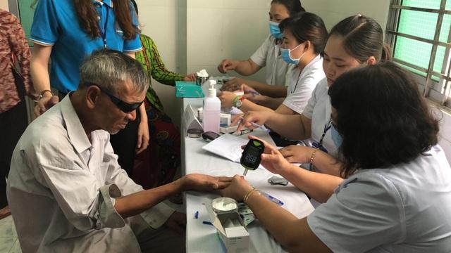 Cán bộ Bảo Việt Nhân Thọ tận tình hỗ trợ người dân đến khám bệnh.