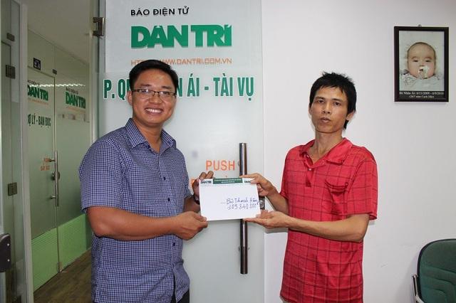 Nhà báo Ngô Công Quang, Phó Trưởng VP đại diện báo Dân trí tại TP.HCM trao tiền bạn đọc giúp đỡ cho gia đình anh Thanh Hận