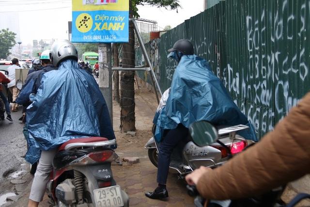 Nhiều xe máy lách qua khe vỉa hè nhỏ hẹp trên đường Lê Văn Lương.