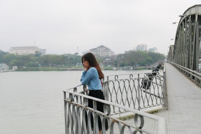 Một thiếu nữ dừng chân ngắm cảnh trên cầu