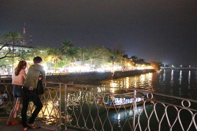Một cặp đôi hóng gió ngắm sông Hương trên cầu vào đêm