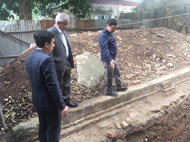PGS Tống Trung Tín cùng GS Phan Huy Lê và Giám đốc Trung tâm Di sản Hoàng thành Thăng Long tham quan hố khai quật. Ảnh: Tùng Long.