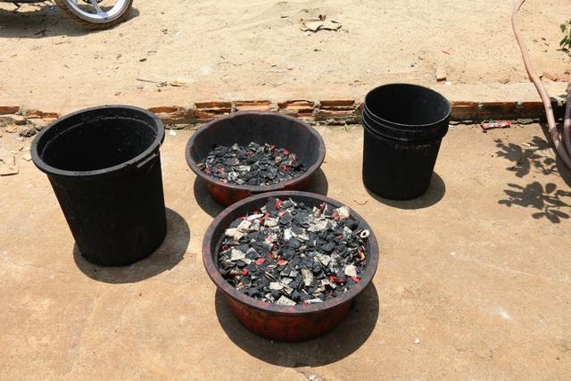 Một khu chứa nguyên liệu bao gồm vỏ cà phê, bột đá, bột pin con ó, nhiều thùng đựng nước màu đen, máy trộn và lò sấy.