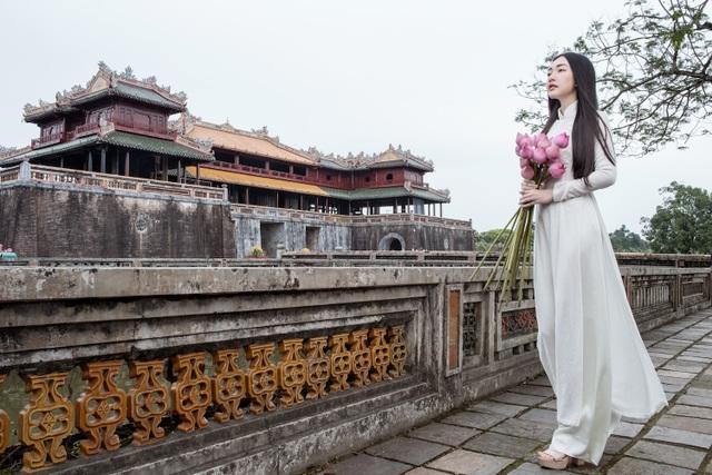 Người đẹp duyên dáng với áo dài trắng mộc mạc, ôm bó sen hồng bước đi giữa khung cảnh trầm mặc, cổ kính.