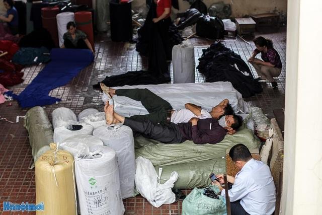 Giấc ngủ tranh thủ của những cửu vạn ở khu vực hành lang chợ.