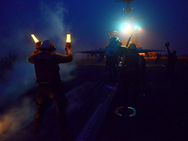 Các thủy thủ hướng dẫn kỹ thuật cho máy bay F/A-18C Hornet cất và hạ cánh trên tàu sân bay USS John C. Stennis. (Ảnh: US Navy)