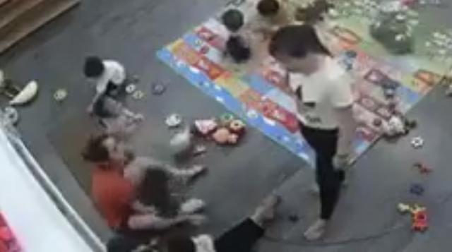 Cô bắt đầu hành hạ cháu bé. Cô giáo mặc áo trắng đứng nhìn như không có chuyện gì xảy ra.
