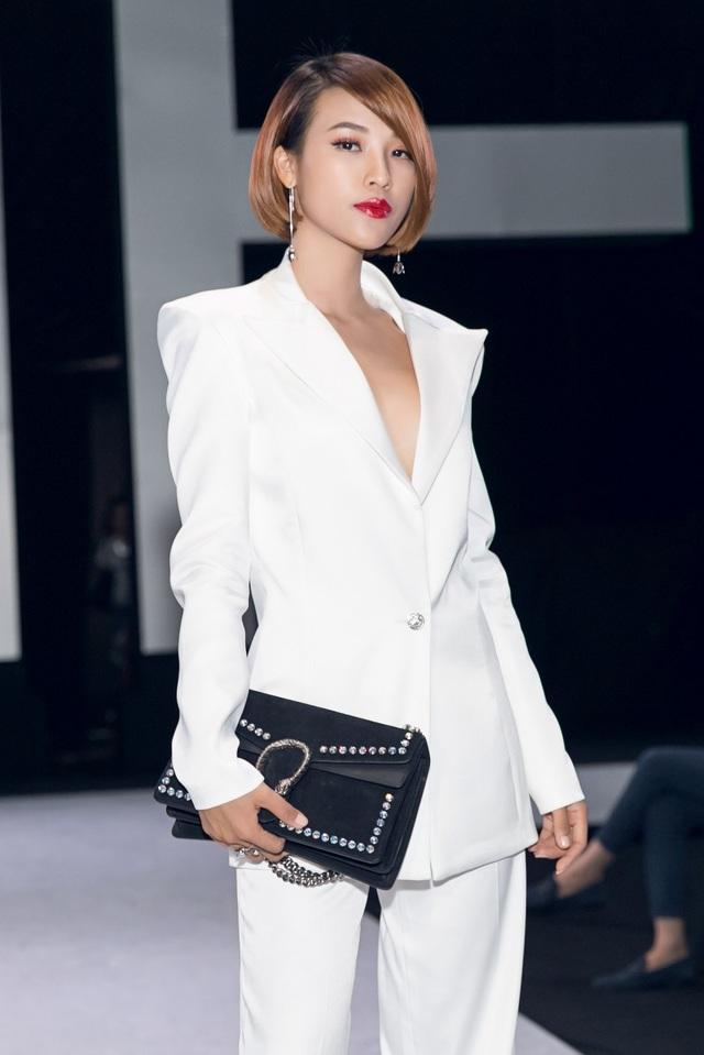 """Tạm biệt những chiếc váy xòe nữ tính, Hoàng Oanh bất ngờ xuất hiện với bộ vest trắng. Chi tiết khoét sâu ở cổ áo giúp """"Dung đại ca"""" của """"Tháng năm rực rỡ"""" cá tính hơn nhưng cũng không kém phần quyến rũ, gợi cảm. Đặc biệt, chính mái tóc ngắn vốn trở thành thương hiệu góp phần mang đến sự nổi bật cho Hoàng Oanh. Đặc biệt, trong lần xuất hiện này, Hoàng Oanh phối bộ trang phục cá tính với chiếc túi hàng hiệu đắt đỏ - điều hiếm thấy ở cô. (Ảnh: Kiệt Võ)."""