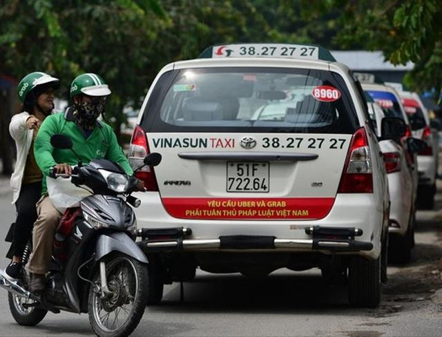 Nhiều xe taxi Vinasun ở TP.HCM từng dán biểu ngữ phản đối Uber và Grab.