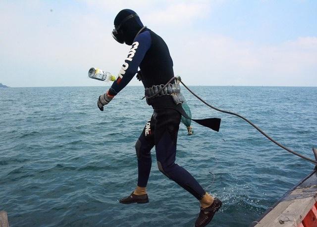 Sau khi mặt đầy đủ dụng cụ, các thợ lặn nhảy xuống nước.