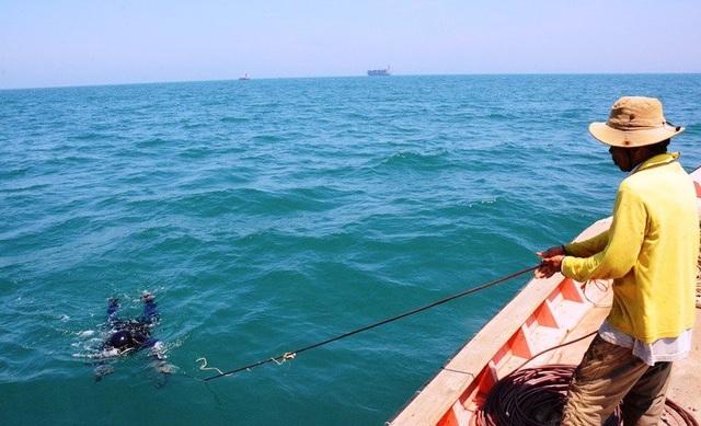 Thợ lặn đang được người hậu cần lôi lên từ đáy biển.