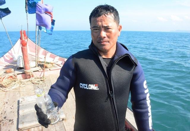 Anh Lê Xuân Phú, bắt được 3 con tôm nhí (được nhốt trong chai nhựa).