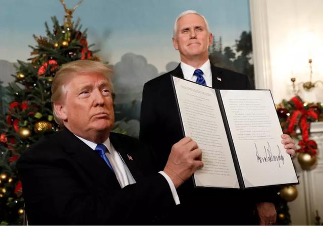 Tổng thống Mỹ Donald Trump (ngồi) giơ cao bản tuyên bố rằng Mỹ công nhận Jerusalem là thủ đô Israel và sẽ di chuyển đại sứ quán đến đây, tại Nhà Trắng ngày 6-12-2017, đứng bên cạnh là Phó Tổng thống Mỹ Mike Pence. Ảnh: REUTERS