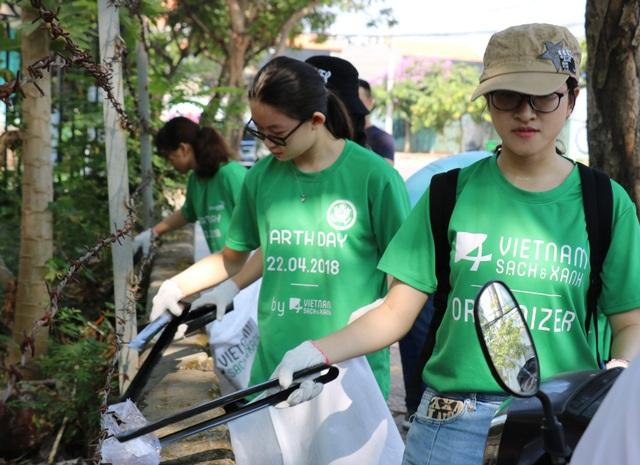Những tình nguyện viên nữ không ngại ngần nhặt rác ở các ống cống để làm sạch môi trường