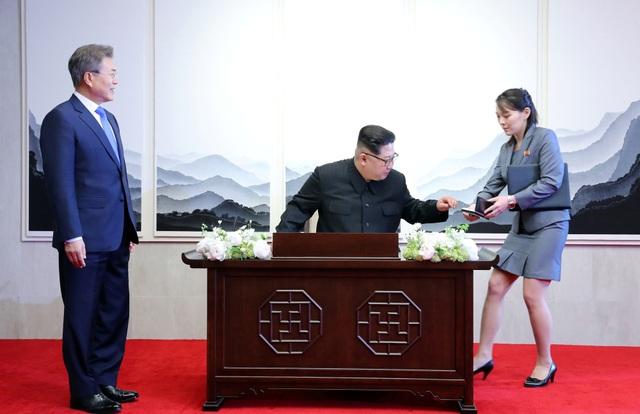 Bà Kim Yo-jong đưa bút cho nhà lãnh đạo Triều Tiên để ông viết trong sổ lưu niệm tại Nhà Hòa bình, nơi diễn ra hội nghị thượng đỉnh liên Triều. (Ảnh: Reuters)
